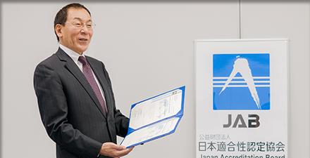 ウェブアクセシビリティ適合性評価機関の認定書を受け取る加藤社長。